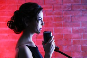 Beautiful brunette singing woman on brick wall background